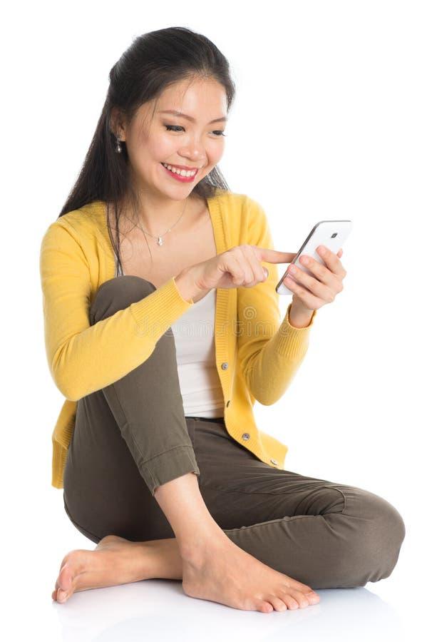 El mandar un SMS asiático de la hembra foto de archivo