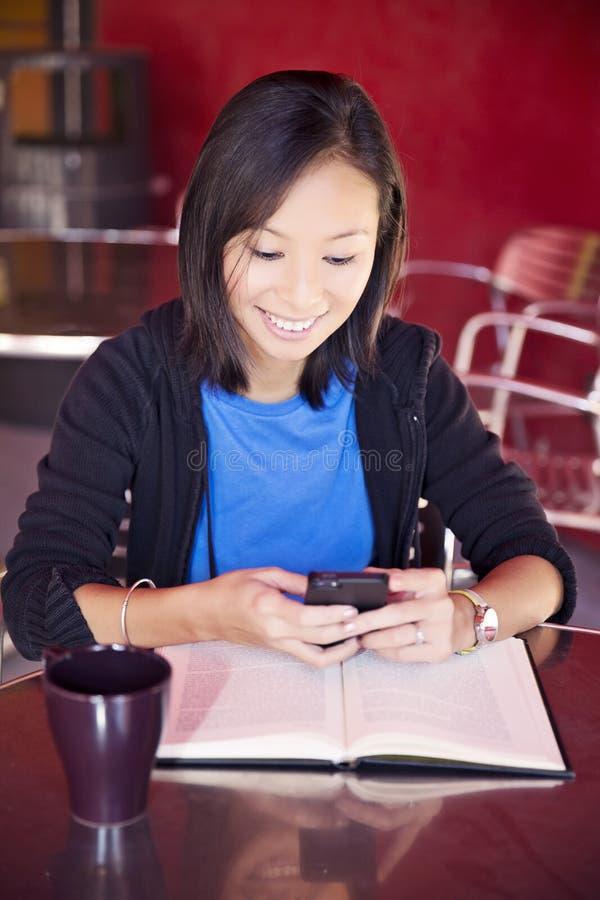 El mandar un SMS asiático del estudiante universitario fotografía de archivo