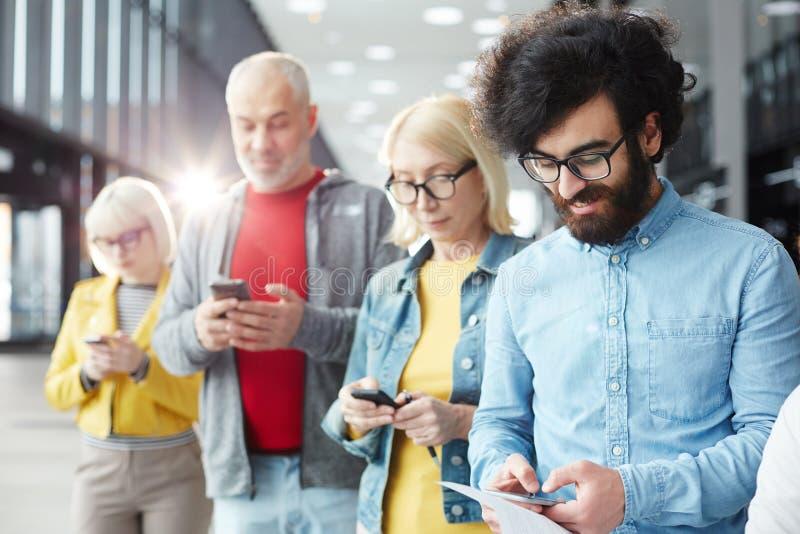 El mandar un SMS de la gente foto de archivo libre de regalías