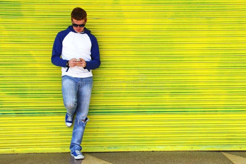 El mandar un SMS en amarillo imagen de archivo libre de regalías