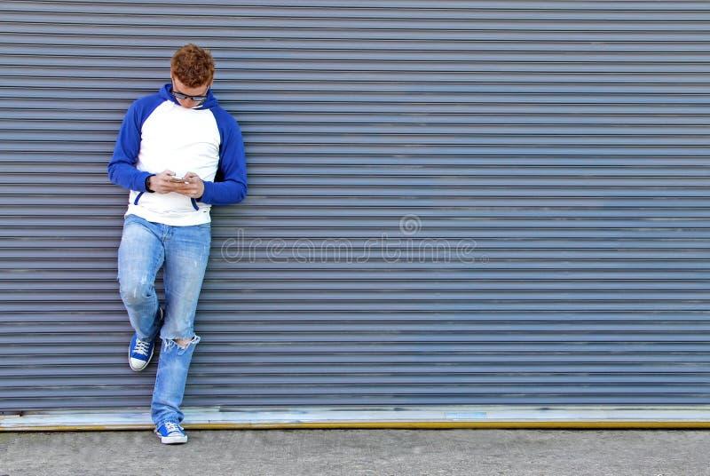 El mandar un SMS en backgropund azul-gris imágenes de archivo libres de regalías