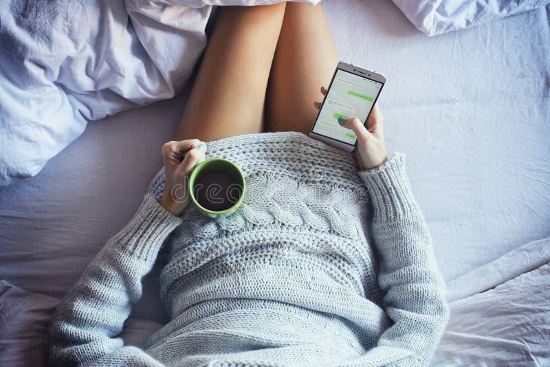 El mandar un SMS en cama foto de archivo libre de regalías
