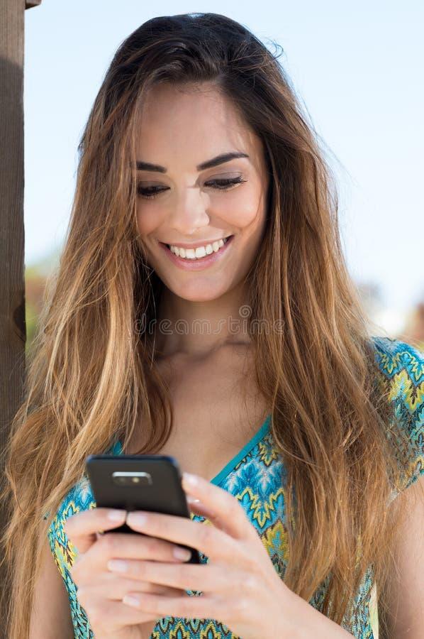 El mandar un SMS feliz de la mujer joven fotografía de archivo libre de regalías