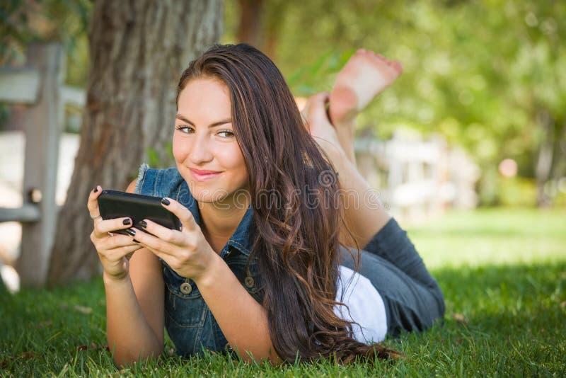 El mandar un SMS femenino adolescente de la raza mixta feliz atractiva en su tel?fono celular fuera de la colocaci?n en la hierba fotografía de archivo