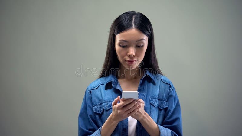 El mandar un SMS femenino asiático usando el smartphone, trabajo en línea distante para las mujeres, negocio imagen de archivo libre de regalías