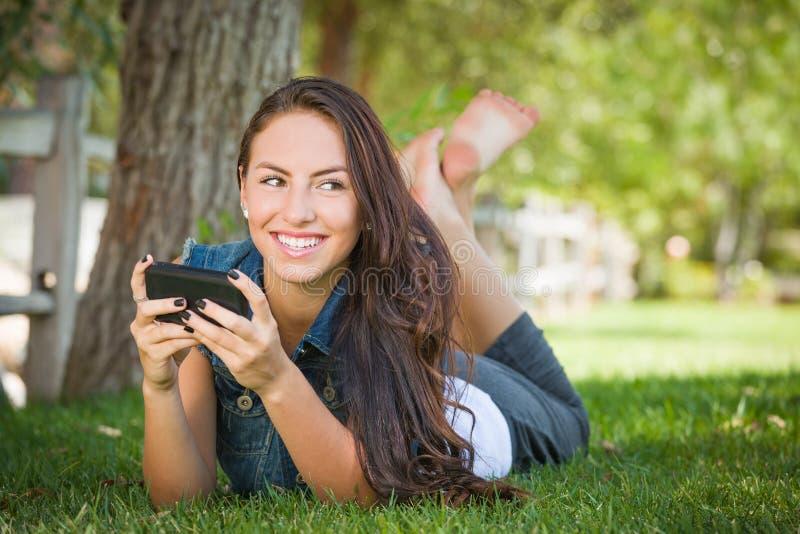 El mandar un SMS femenino joven de la raza mixta feliz atractiva en su célula Pho fotos de archivo