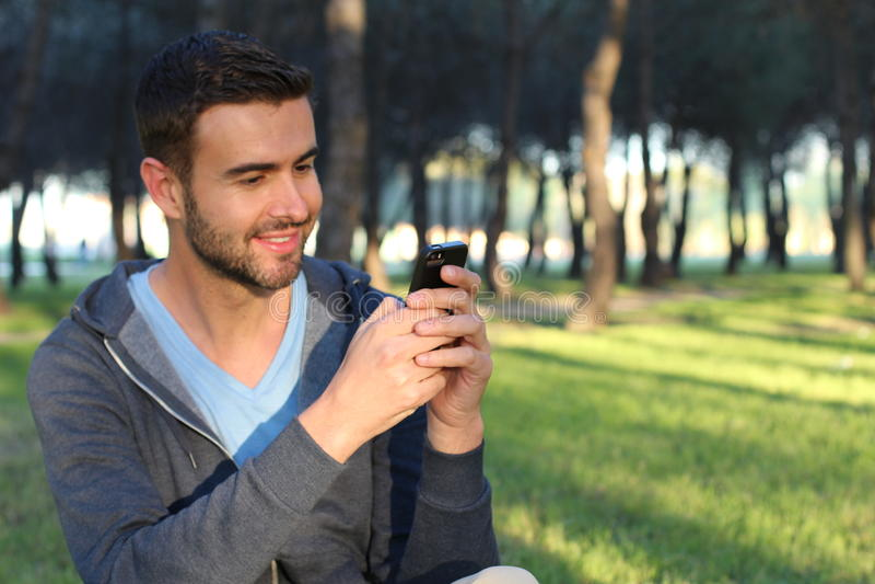 El mandar un SMS masculino alegre en el parque imágenes de archivo libres de regalías