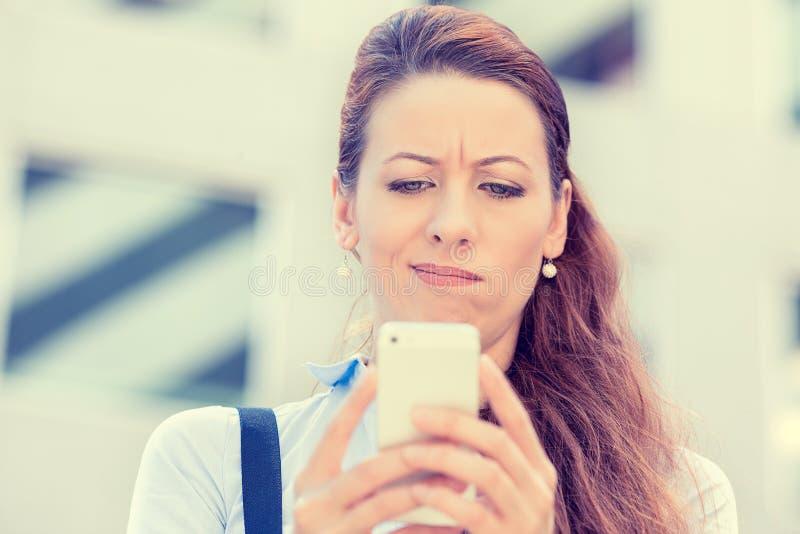 El mandar un SMS que habla de la mujer seria infeliz escéptica triste trastornada en el teléfono móvil fotos de archivo