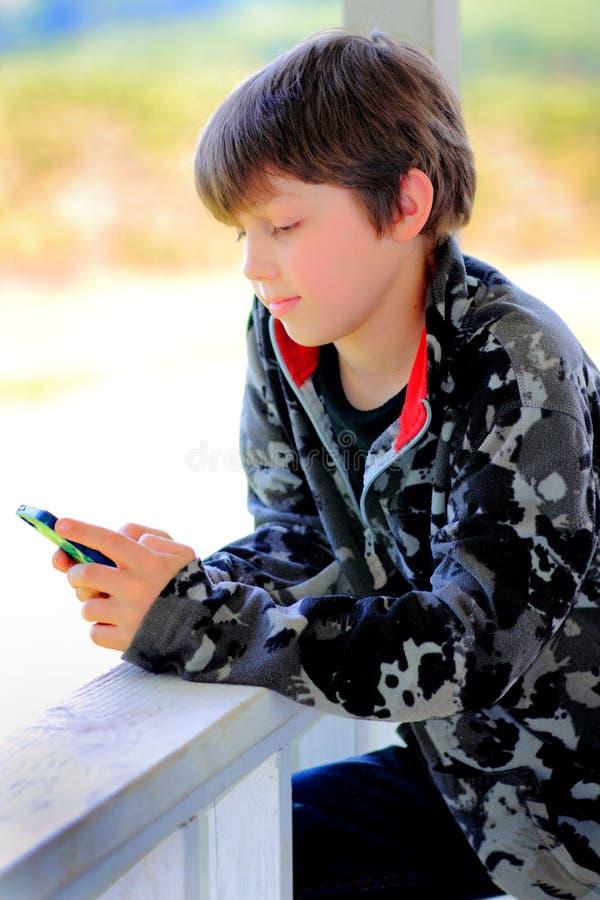 El mandar un SMS relajado del niño foto de archivo