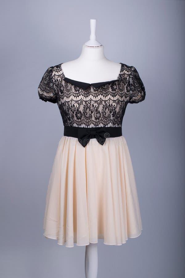 El maniquí de los sastres se vistió en un vestido beige y negro del cordón imagen de archivo