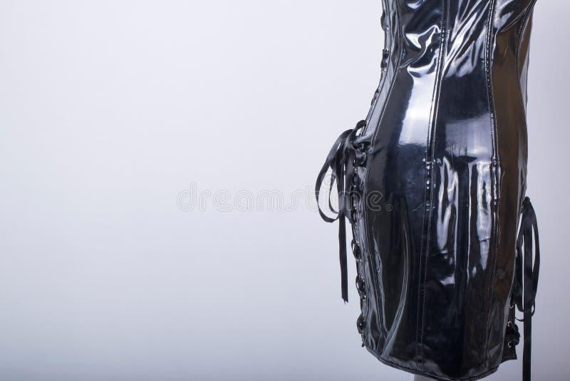 El maniquí de los sastres se vistió en un vestido negro del corsé del PVC fotos de archivo