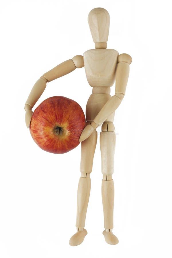 El maniquí de madera sostiene la manzana roja fotografía de archivo