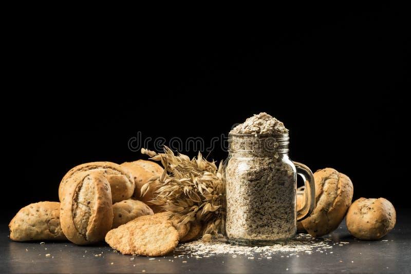 El manojo de la avena, el pan blanco cocido, las galletas y las escamas en la condimentación sacuden fotografía de archivo libre de regalías