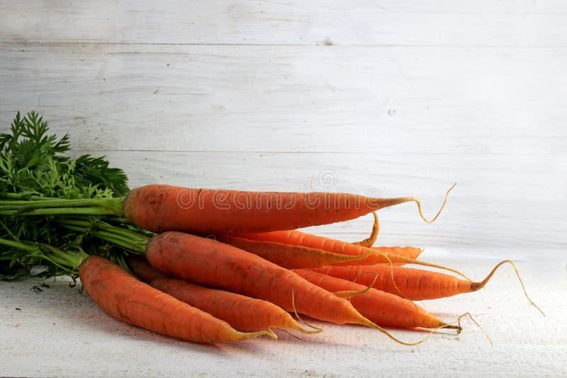 El manojo de la zanahoria en blanco pintó la madera rústica con el espacio de la copia imagen de archivo