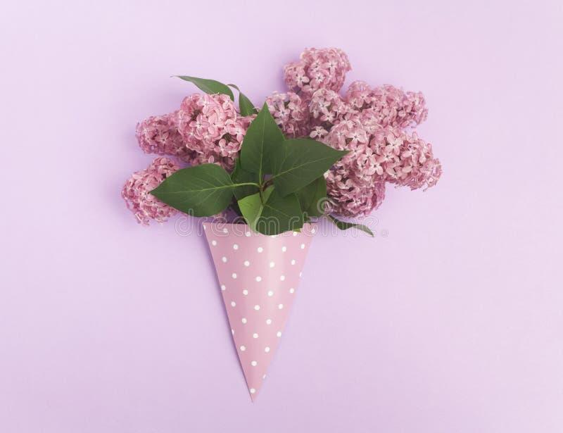 El manojo de lila florece en el cono de papel en fondo púrpura desde arriba, completamente endecha fotos de archivo