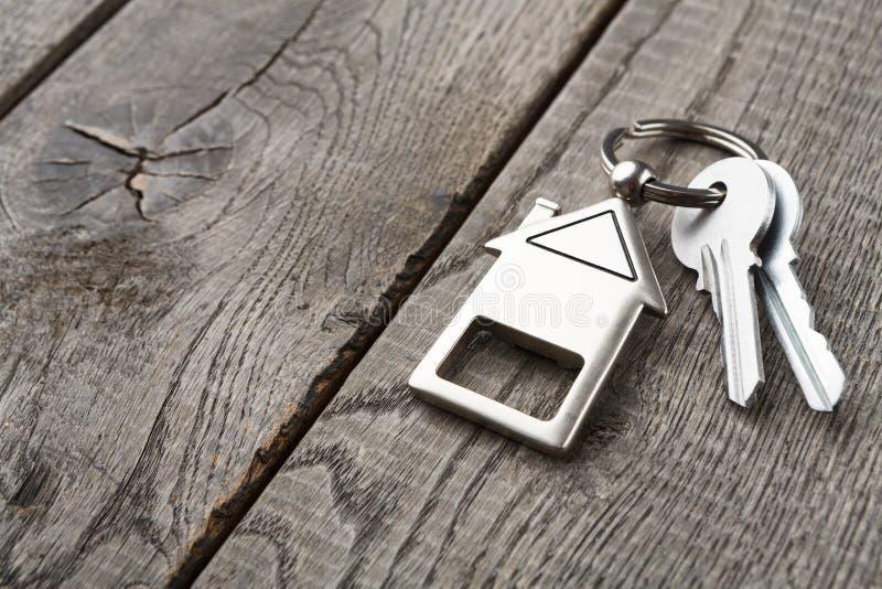 El manojo de llaves con la casa formó llavero en la madera rústica fotografía de archivo