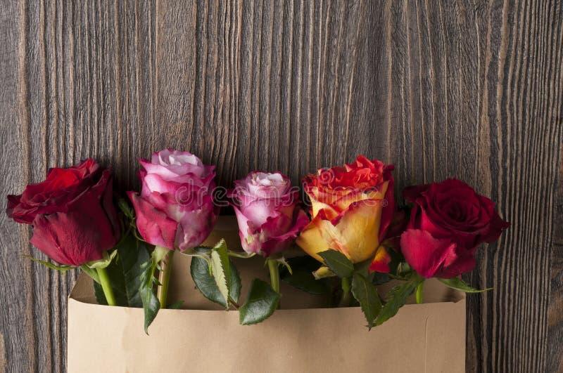 El manojo de rosa multicolora florece en el sobre de papel sobre b de madera fotografía de archivo