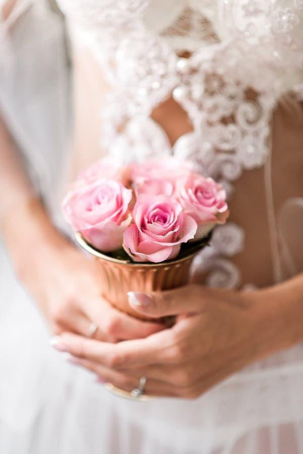 El manojo de rosas en novias trata las manos con suavidad fotografía de archivo