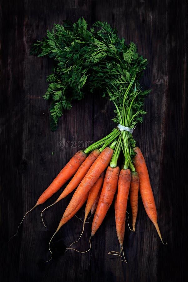 El manojo de zanahorias con verde fresco se va en un de madera rústico oscuro fotos de archivo libres de regalías