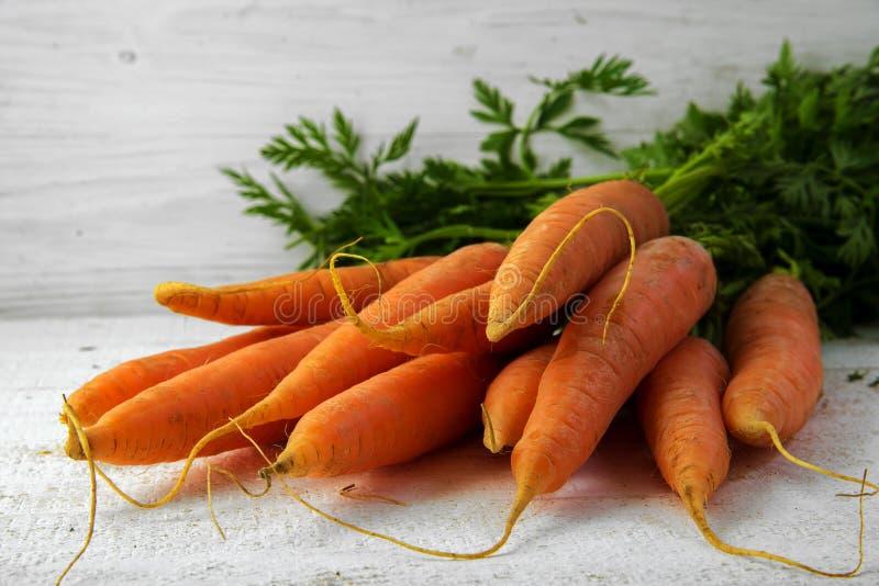 El manojo de zanahorias frescas con verde se va en el blanco pintado rústico imagen de archivo libre de regalías