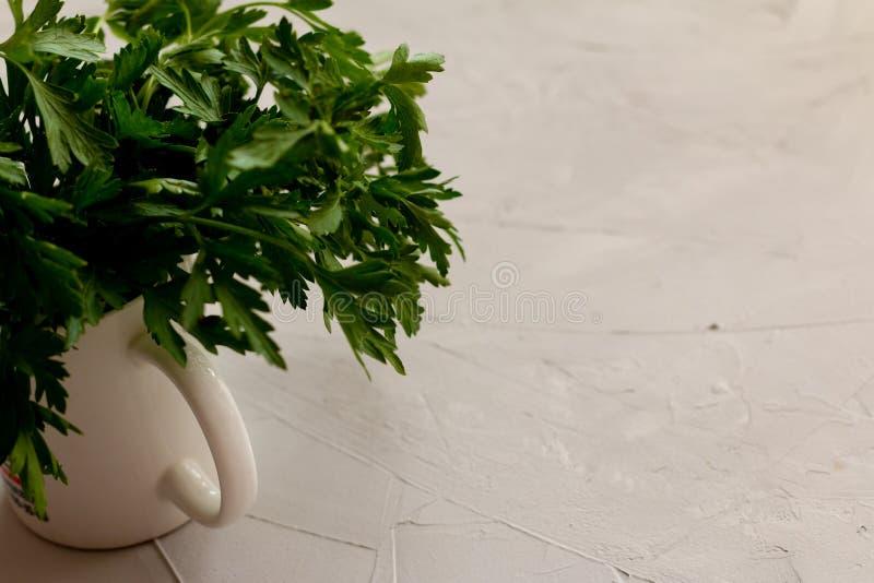 El manojo verde fresco del perejil en un pote, alista para cocinar fotografía de archivo