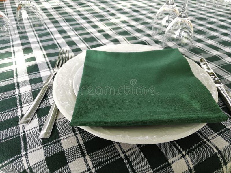 El mantel blanco y verde típico puso en una tabla del restaurante fotografía de archivo