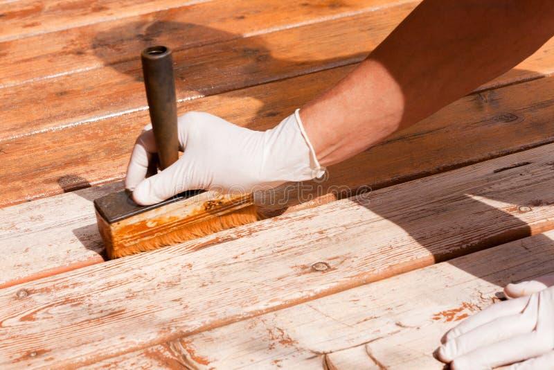 El mantenimiento de la cubierta aplica la mancha en decking de madera fotos de archivo libres de regalías