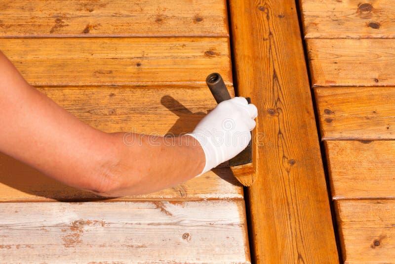 El mantenimiento de madera de la cubierta aplica la mancha en decking fotos de archivo