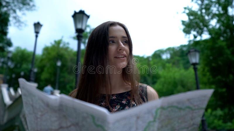 El mapa de mirada turístico de la muchacha en, encuentra con éxito manera a la atracción histórica imagen de archivo