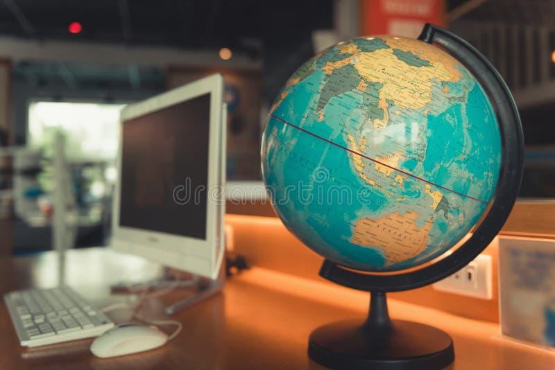 El mapa del mundo y el ordenador del globo en la mesa, en todo el mundo viajan imágenes de archivo libres de regalías