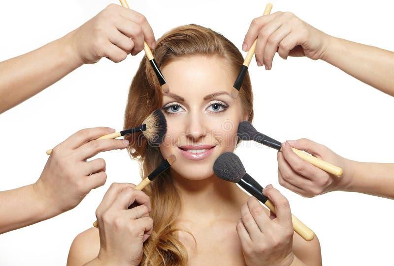 El maquillaje aplica cerca de cara atractiva muchas manos con brocha foto de archivo
