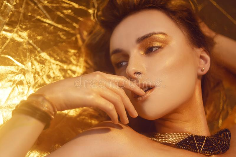 El maquillaje, Art Beauty Face y los labios de la moda del oro componen en brocado de oro Retrato de oro de la cara de la mujer d foto de archivo libre de regalías
