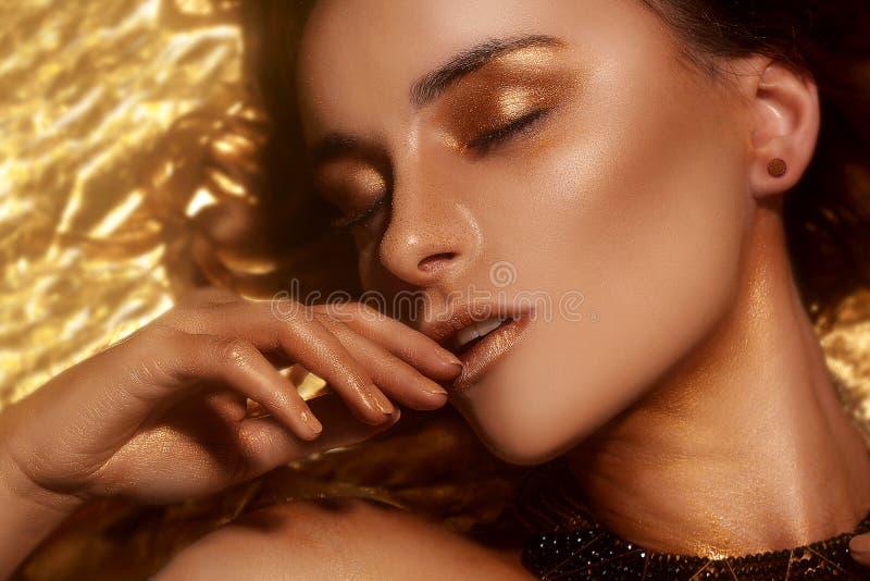 El maquillaje, Art Beauty Face y los labios de la moda del oro componen en brocado de oro Retrato de oro de la cara de la mujer d fotos de archivo libres de regalías