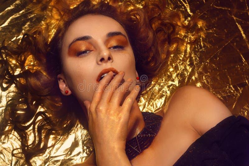 El maquillaje, Art Beauty Face y los labios de la moda del oro componen en brocado de oro Retrato de oro de la cara de la mujer d imagen de archivo libre de regalías