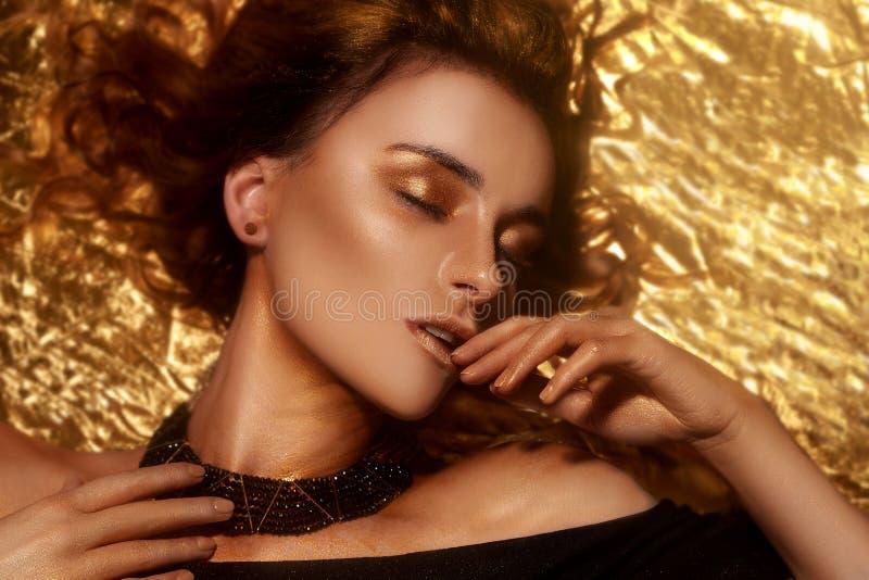 El maquillaje, Art Beauty Face y los labios de la moda del oro componen en brocado de oro Retrato de oro de la cara de la mujer d imágenes de archivo libres de regalías