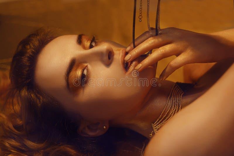 El maquillaje, Art Beauty Face y los labios de la moda del oro componen en brocado de oro Retrato de oro de la cara de la mujer d imagenes de archivo