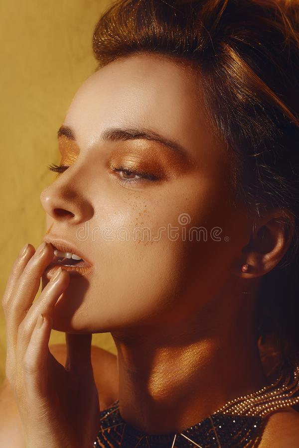 El maquillaje, Art Beauty Face y los labios de la moda del oro componen en brocado de oro Retrato de oro de la cara de la mujer d fotos de archivo