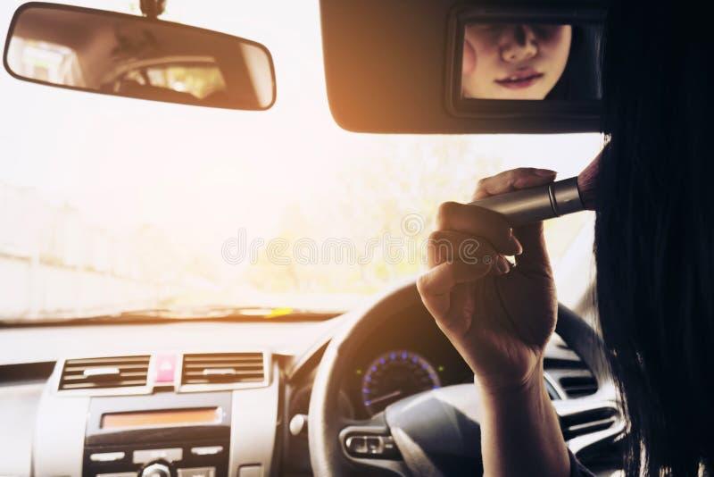El maquillaje de la mujer su cara usando se ruboriza cepillo mientras que conduce el coche fotos de archivo libres de regalías