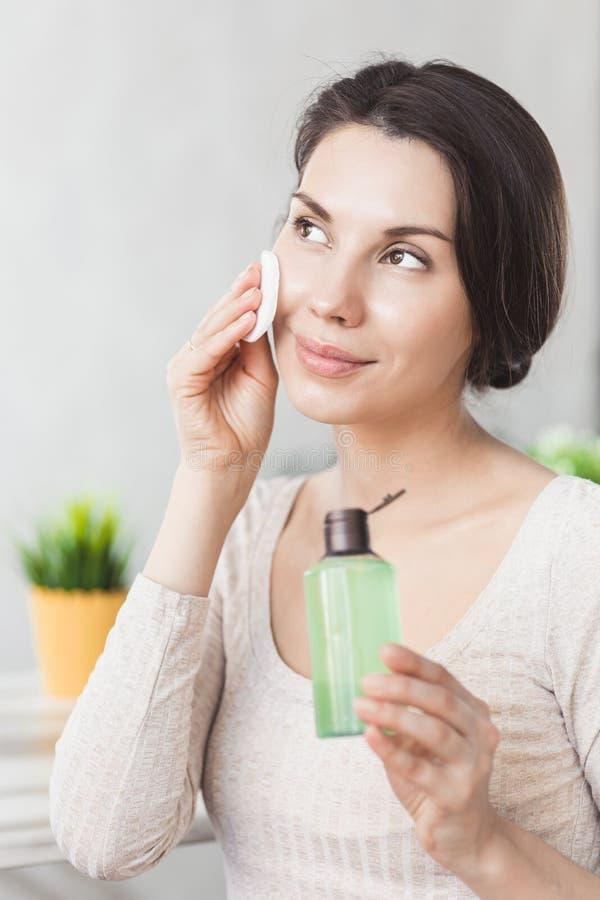 El maquillaje quita cuidado de piel Mujer del primer que sostiene el cosmético líquido de la esponja de algodón y del removedor d foto de archivo libre de regalías