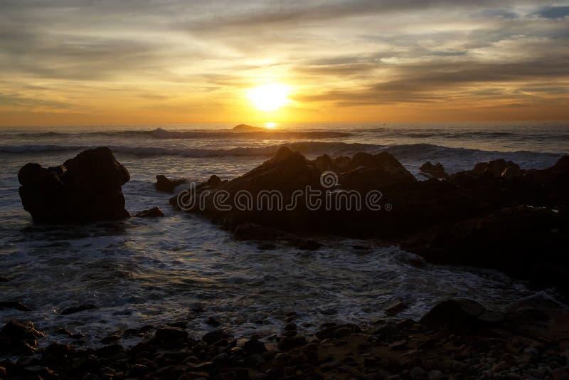 El mar agita estrellarse sobre las rocas en puesta del sol imagenes de archivo
