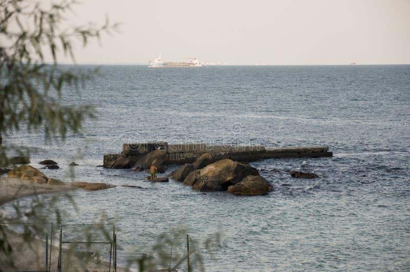 El Mar Negro Agua sin ondas y poco barco lejos calma Principalmente tiempo nublado Color azul y gris Antes de lluvia imagen de archivo