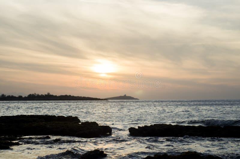 El mar oscila la luz de la puesta del sol fotos de archivo