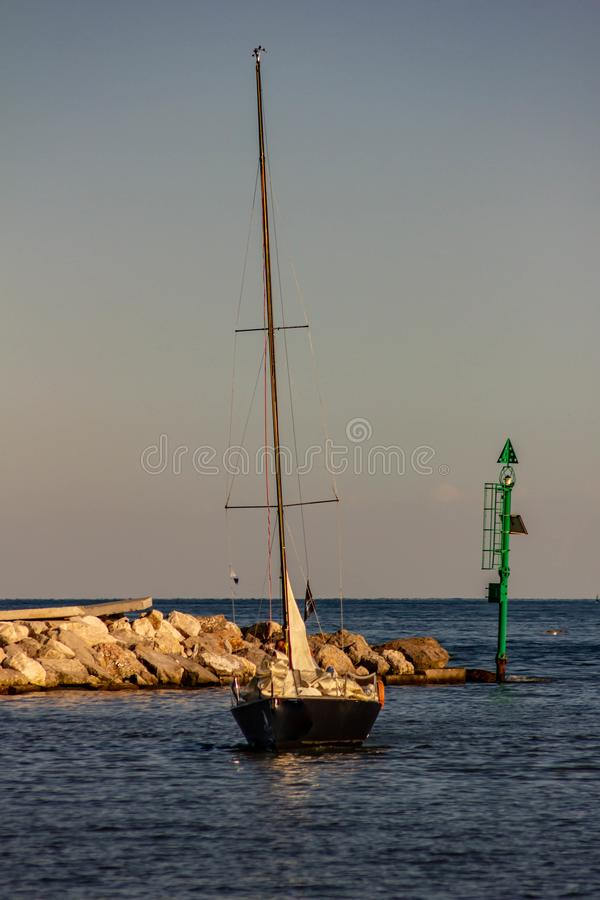 El mar, el sol casi está en la puesta del sol, un velero vuelve para virar hacia el lado de babor después de un paseo Fondo hermo imágenes de archivo libres de regalías