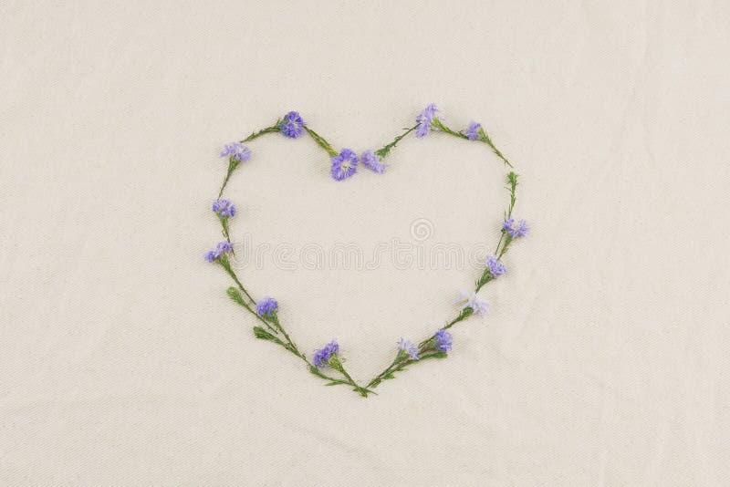 El marco de la forma del corazón hecho del cortador púrpura florece fotos de archivo libres de regalías