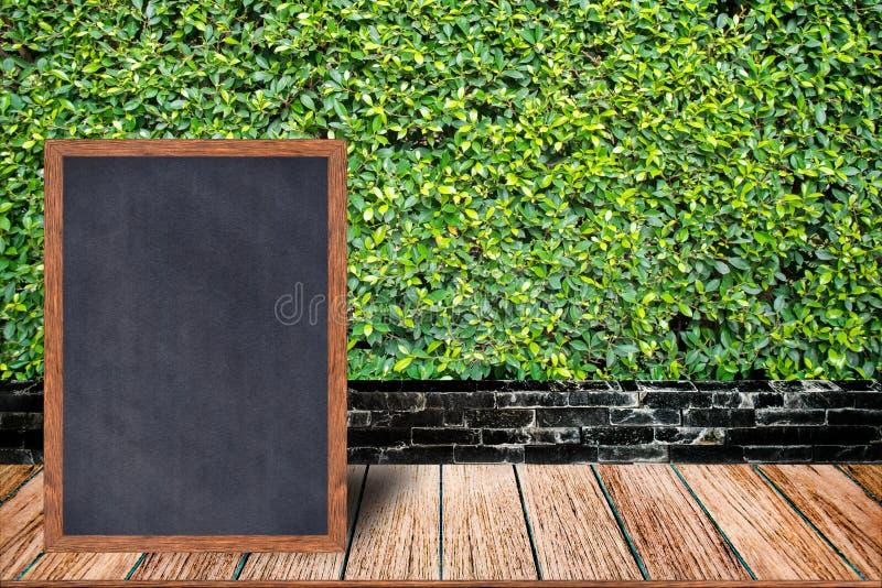 El marco de madera de la pizarra, el menú de la muestra de la pizarra en la tabla de madera y la hierba emparedan el fondo foto de archivo