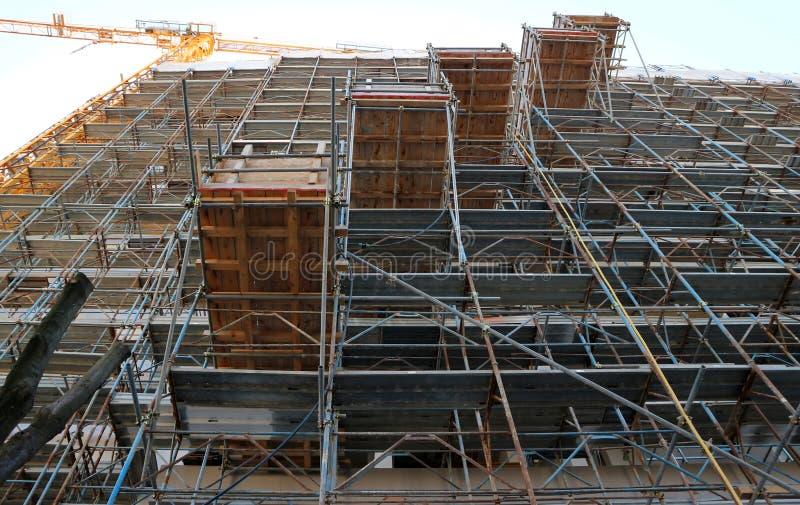 El marco del andamio, con cinco plataformas de trabajo temporal simétricas externas, cubre completamente la fachada constructiva  foto de archivo libre de regalías