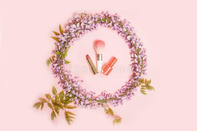 El marco del círculo del maquillaje de los cosméticos y las flores hermosas de la glicinia ramifican con los brotes de los flores imágenes de archivo libres de regalías