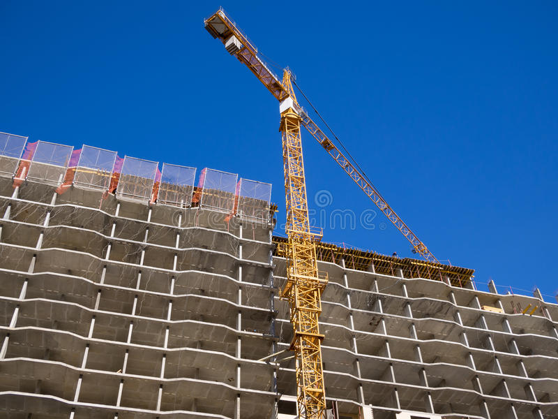 El marco un edificio de apartamentos monolítico y grúa próximo imagenes de archivo