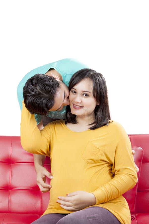 El marido cariñoso sorprende a la esposa embarazada con el presente y un beso fotos de archivo libres de regalías