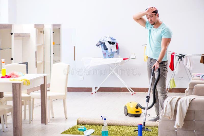 El marido del hombre joven que hace limpiar con la aspiradora en casa foto de archivo
